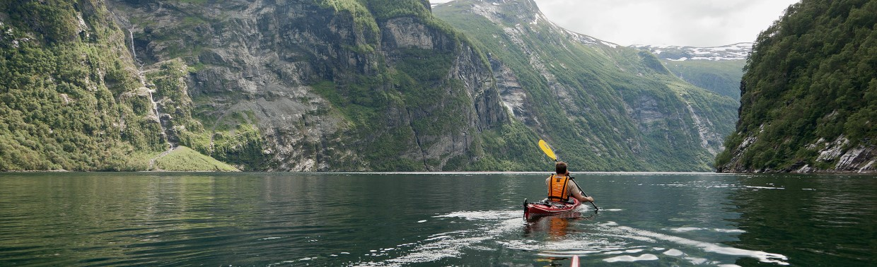 Kayaking in Geirangerfjord, people paddling kayak, mountain walls to the left and right.