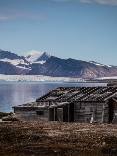Old wooden cabin in Ny-Ålesund, sea and partly snow covered mountains in  the background.