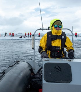 Hurtigruten Expedition team member in a small boat during a landing.