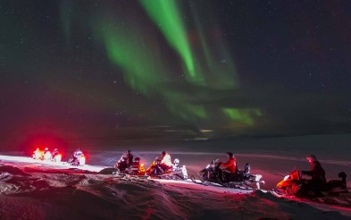 Snowmobiles under the Northern Lights